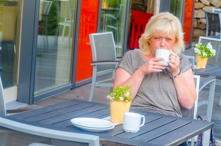 Woman sitting at a sidewalk cafe relaxed at a table, enjoying the day. photo