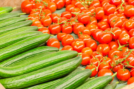 differed: Various tomatoes and cucumbers for sale at a farmers market