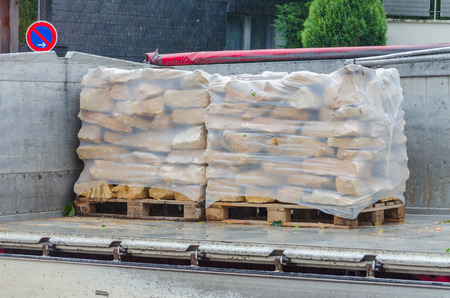 Pallets with sand stones are delivered and unloaded from a truck. photo