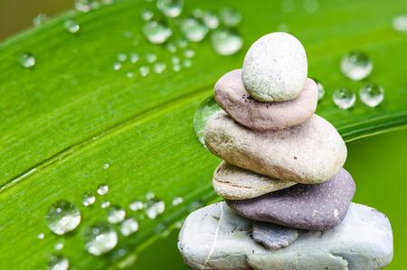Balance, balance, serenity stone pile with bamboo leaf. photo