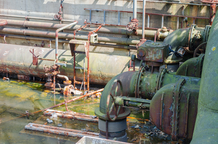 industrially: Water basin with rusted pipes and valves.
