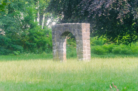 rely: Stone, gate, arch, arched with passage stands alone rely on a large meadow.