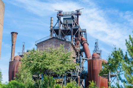 dysentery: Old rusty abandoned blast furnace plant against a blue sky
