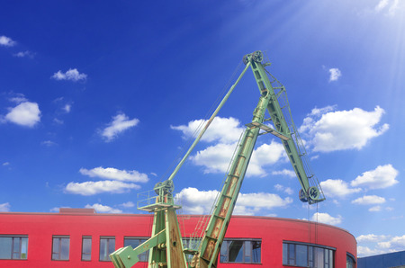 Old harbor crane in the city port of Duisburg Germany in front of a modern day office building