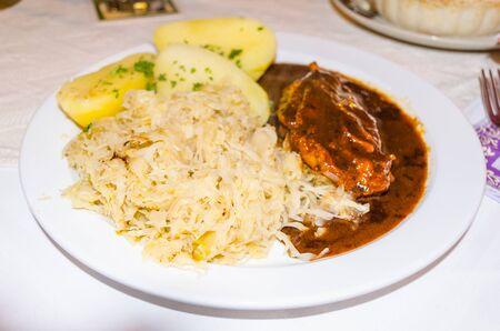 spanferkel: Spanferkel Eisbein mit Kartoffeln und Sauerkraut.