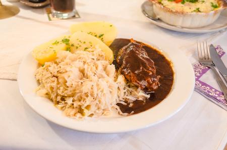 spanferkel: Spanferkelkeule mit Kartoffeln und Sauerkraut.