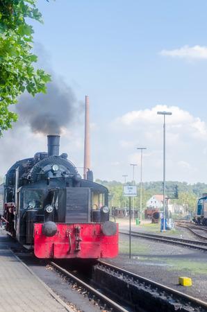 Vertrek en achteraanzicht van een stoomlocomotief onder volle stoom bij de uitgang van het station.