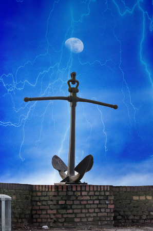 disastrous: Anchor on a wall. Against a dramatic cloudscape with lightning and moon.