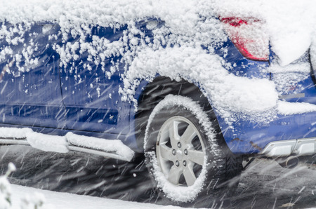 tire tracks: Close-up of SUVs parked in the snow storm. Stock Photo