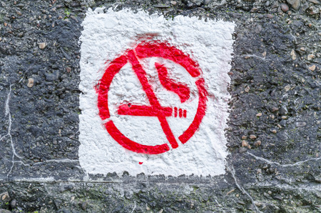 crossed cigarette: Graffiti smoking ban on an old concrete wall.