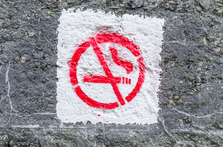 prohibitions: No smoking symbol sprayed on an ancient concrete wall.