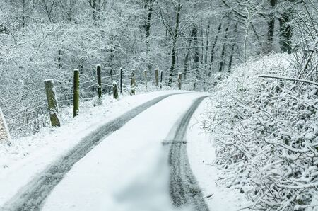 Country Road after snowfall. In the middle  a fresh vehicle lane.