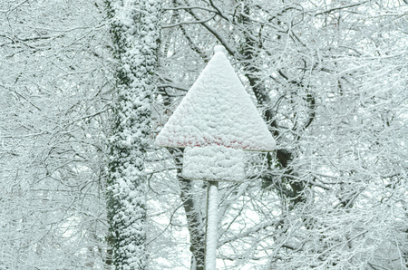barely: Traffic sign covered with snow barely visible.