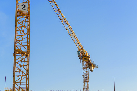 housing problems: Two Construction cranes on a construction site against a blue sky.