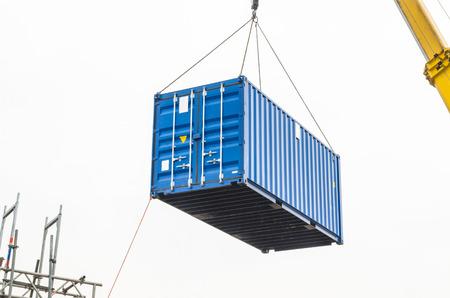 camion grua: Contenedores azules de construcción, contenedores de carga, contenedores habitables en una grúa de carga.