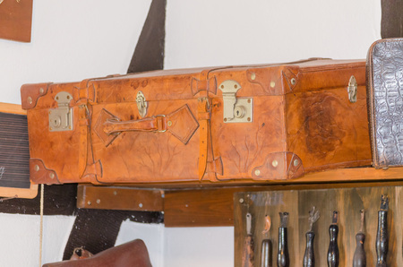 Very old used travel suitcase with scuffs.