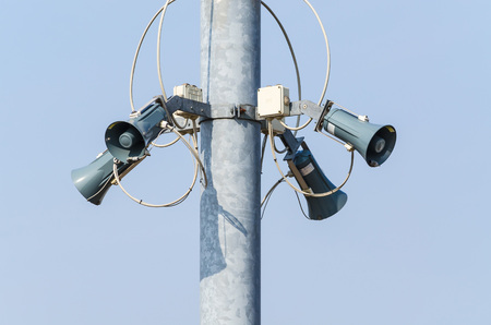 public address: Speaker system against a mounting pole against a blue sky. Stock Photo