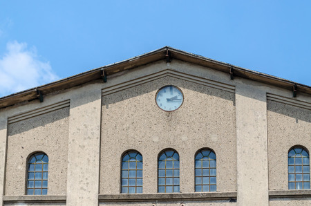 behind the scenes: Factory building facade with clock in front of blue sky.