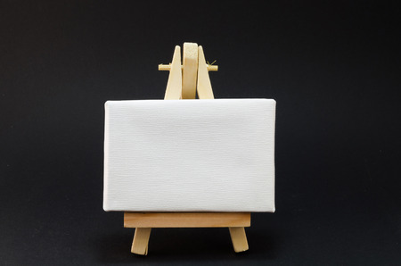 creativ: Miniature artist easel, isolated on black background.