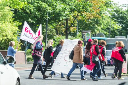 verdi: Ratingen, Nrw, Germany - MAY 18, 2015: Participants of a demonstration, warning strike in Ratingen. Group of people with flags and banners of the German trade union Verdi. Announces the Steik in German kindergartens and nursery school.