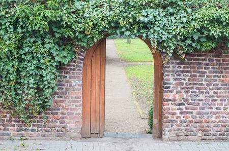 Ein Eingangstor in einer Wand in einem Park. Hinter der offenen Tür ist ein Weg.