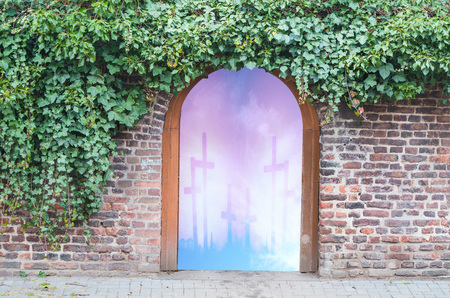 openly: Photomontage, an entrance gate in a wall in a park. Behind the gate open the gateway to heaven. Stock Photo