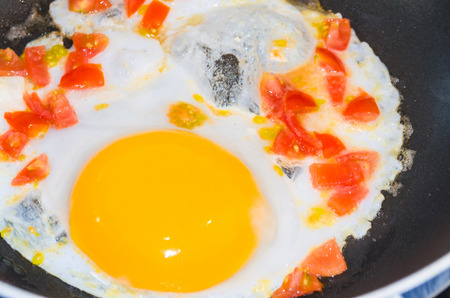 fried eggs: Preparation breakfast. Fried eggs with peppers and tomatoes in a pan. Stock Photo