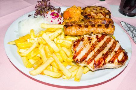 carnes: T�pico plato de barbacoa griega con diversas carnes, ensalada y papas fritas. Foto de archivo