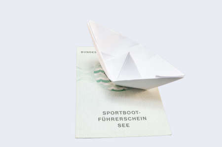 small paper: Document from the German boat driving license lake. With small paper ship as a symbol. Stock Photo