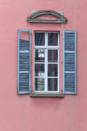 red shutters: An old window with blue shutters opened at an old house. Red facade. Stock Photo