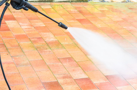 Outdoor floor cleaning and building cleaning with high pressure water jet. Фото со стока
