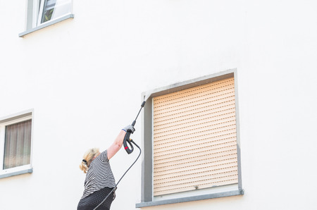 water jet: Exterior cleaning and building cleaning a gable wall with high pressure water jet. Stock Photo