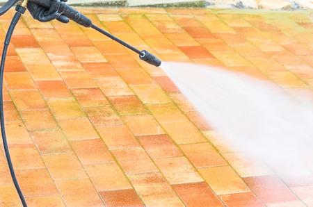 Outdoor vloer schoonmaken en gebouw reinigen met hoge druk waterstraal.