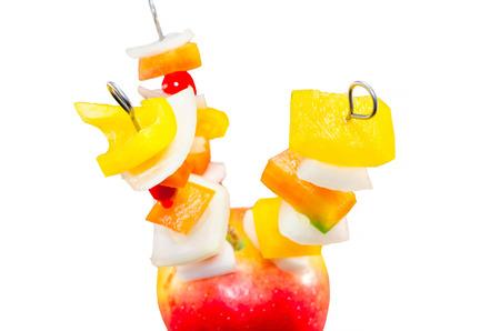 brochetas de frutas: Brochetas de frutas ricas en vitaminas en una manzana contra el fondo blanco. Foto de archivo