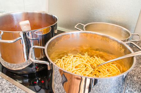 cooktop: Three pots on a ceramic glass cooktop .In front saucepan spaghetti are. Stock Photo