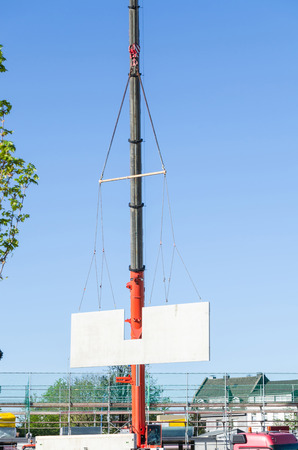 prefabricated house: Mobile Crane car on a construction site. Lifts up a concrete wall.
