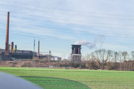 Old power plant on a greenfield site against a blue sky.