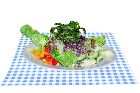 plato de ensalada: Plato de ensalada vegetariana en azul pa�o blanco de mesa, delante de fondo blanco.