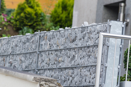gabion mesh: Gabions filled with natural stone as a demarcation to the neighboring properties.