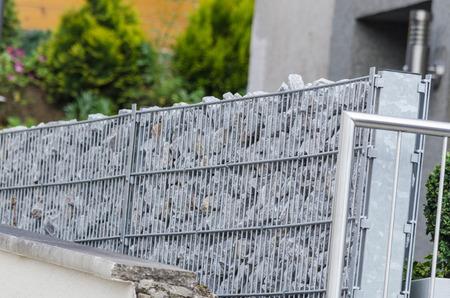 Schanskorven gevuld met natuursteen als een afbakening van de naburige eigendommen. Stockfoto