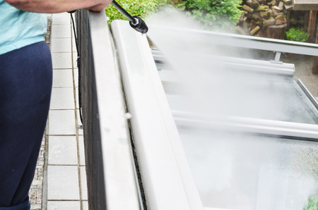 Exterior cleaning and building cleaning a glass roof with high pressure water jet. Stockfoto