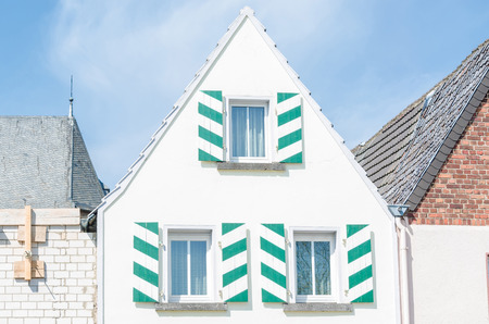 house gable: White House front gable with shutters in white green. Blue sky with clouds.
