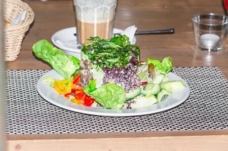 salad plate: Vegetarian salad plate on a tablecloth in the background, a latte. Archivio Fotografico