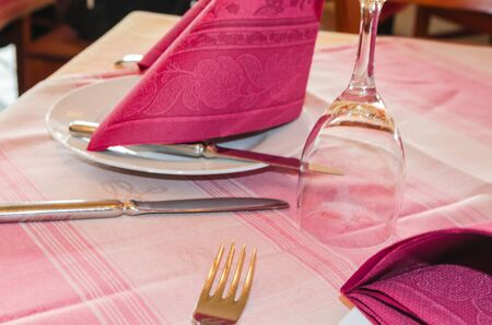 Rustic table laid in a Pizzeria.Restaurant Tischgedeck: napkin, wine glass, plates and cutlery. Standard-Bild