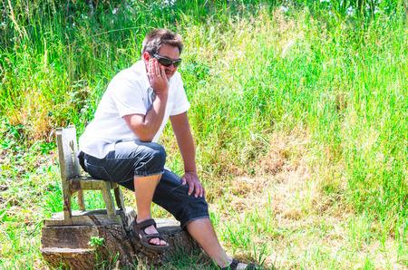 silla de madera: Hombre en actitud pensativa en una peque�a silla de madera. Foto de archivo