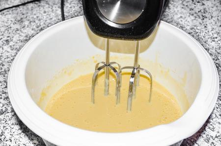 cake mixer: Mix egg, flour and sugar cream in a bowl with mixer motor. Dough for baking a cake