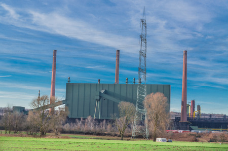 stove pipe: Old industrial facility behind a field against a dramatic sky. Stock Photo
