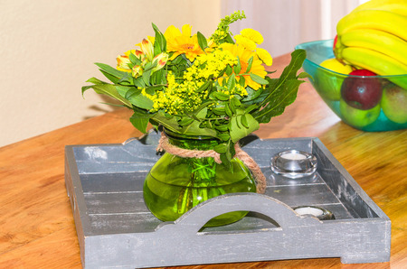 floral arrangement: Colorful floral arrangement on a wooden tray in the background a bowl of fresh fruit.