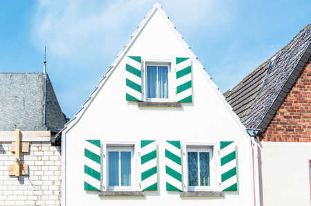 gable: White House front gable with shutters in white green. Blue sky with clouds.