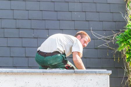 Portrait repairman at work repairing roof Standard-Bild